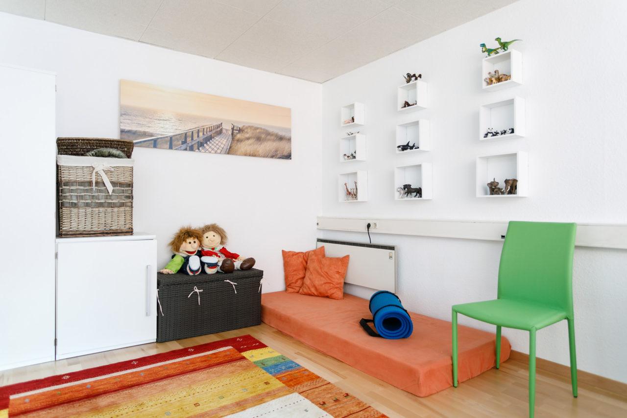 Auf dem Bild ist eine Kinderecke mit Puppen, Pölster und Tierfiguren für die Kinderpsychotherapie zu sehen.