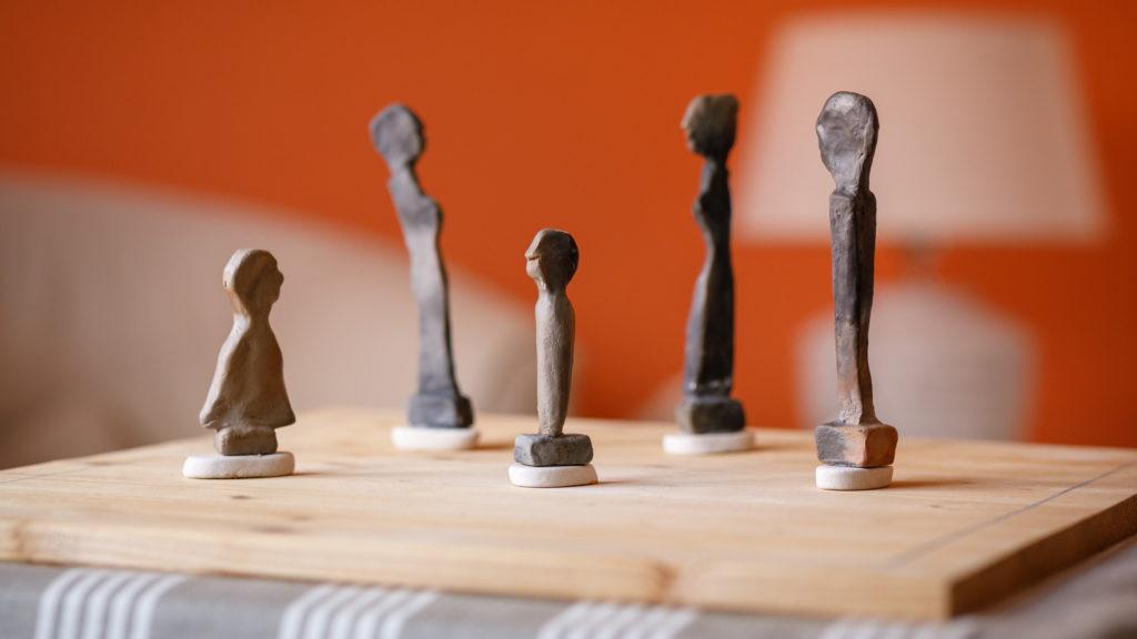 Zu sehen ist ein Familienbrett mit Tonfiguren, die Familienmitglieder darstellen.