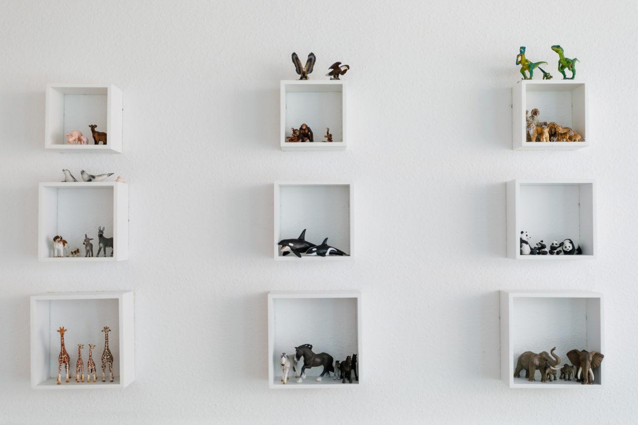 Auf dem Bild sind Wandregale mit Tierfiguren als Materialien für die Psychotherapie zu sehen.