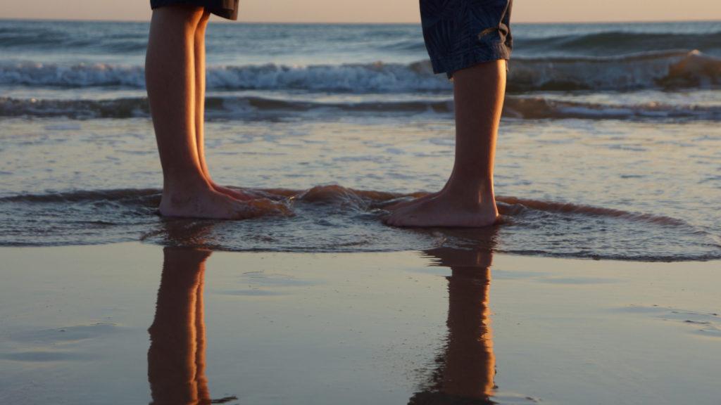 Auf einem Sandstrand sind die Füße von zwei Menschen dargestellt, die sich gegenüber stehen - als Zeichen der Auseinandersetzung miteinander in der Paartherapie und im Paarcoaching.