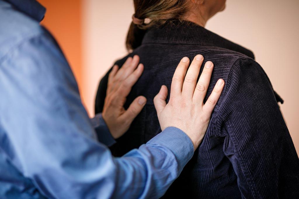 Auf dem Bild wird eine mögliche Patientin von den Händen des Psychotherapeuten am Rücken gestützt. Die Abbildung ist ein Symbol für die Körperpsychotherapie.