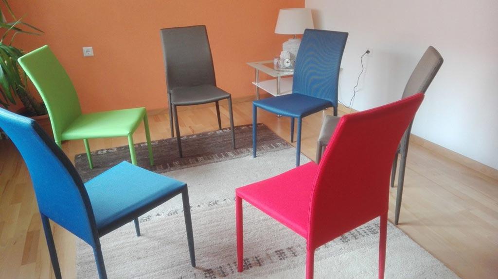 Am Bild sind leere Stühle kreisförmig als Symbol für Gruppenpsychotherapie in der Praxis in Wiener Neustadt angeordnet.