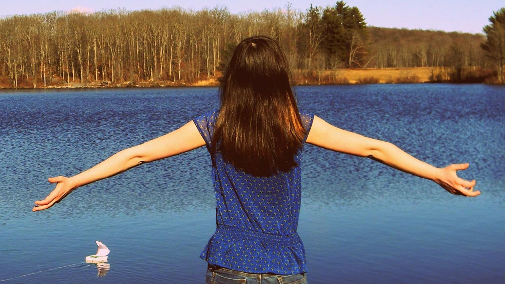 Auf dem Bild ist eine Jugendliche von hinten mit ausgebreiteten Armen vor dem Hintergrund eines Sees zu sehen. Dieses Bild symbolisiert eine mögliche Patientin für die Jugendlichenpsychotherapie.