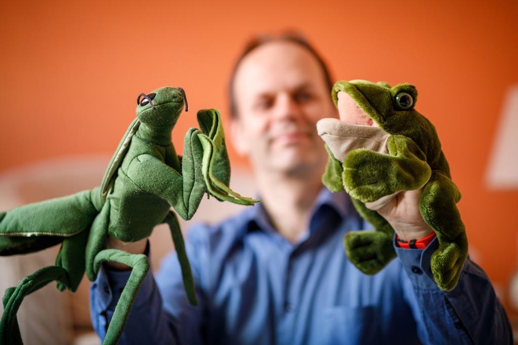 Auf dem Photo ist der Psychologe und Psychotherapeut David Trallori mit zwei Handpuppen als Symbol für die Kinderpsychotherapie zu sehen.