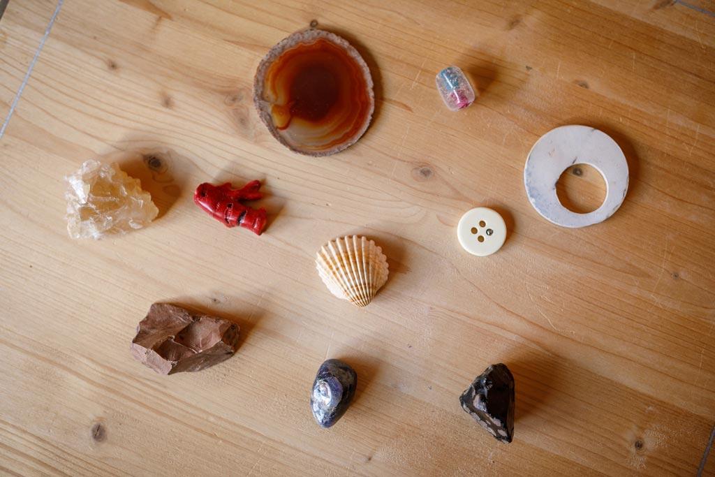 Zu sehen sind Muscheln, Knöpfe, Steine und Glasperlen auf einem Holzbrett als Symbol für die Psychodrama-Psychotherapie.